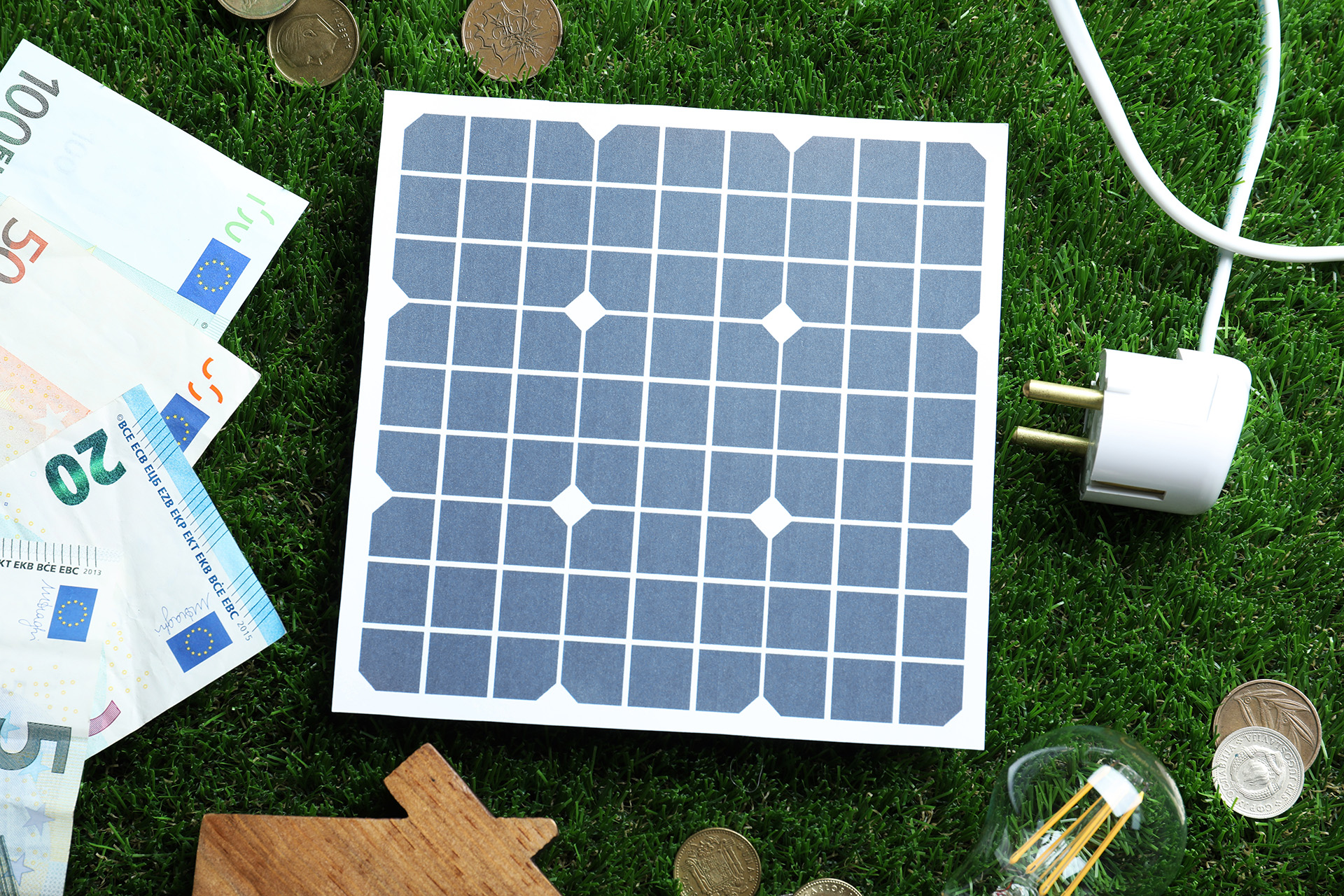 Flat lay composition with solar panel, house model and money on